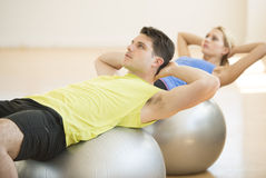 Man Looking Away While Exercising On Fitness Ball At Gym Stock Photos