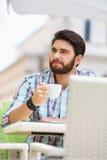 Man looking away while having coffee at sidewalk cafe Stock Photos