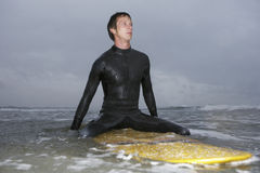 Man Looking Away While Sitting On Surfboard In Water Stock Photos