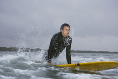 Man Looking Away While Surfing In Water At Beach. Young man looking away while surfing in water at beach stock photo