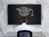 Man  looking on bachelor cap Royalty Free Stock Photos