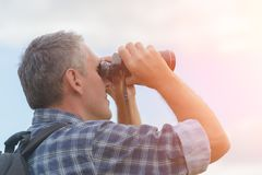 Man looking through binocular Stock Images