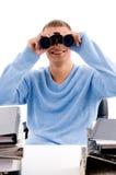 Man looking through binocular at desk Royalty Free Stock Images