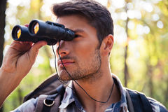 Man looking through binocular in the forest. Portrait of a young man looking through binocular in the forest Royalty Free Stock Image