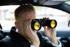 Man Looking Through Binocular. Private Detective Sitting In Car Looking Through Binocular royalty free stock images