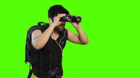 Man looking through binoculars with backpack on green background stock footage