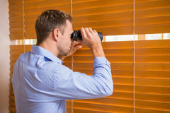 Man looking with binoculars through the blinds Royalty Free Stock Photography