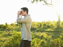 Man Looking Through Binoculars In Field Royalty Free Stock Image