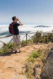 Man looking into binoculars in Madeira viewpoint Stock Photo
