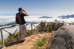 Man looking into binoculars in Madeira viewpoint. A man standing on a viewpoint above clouds, looking into binoculars and admiring a spectacular view from Paul Stock Photos