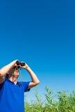 Man looking through binoculars into sky Stock Photo