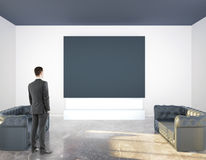 Man looking at blank banner. Businessman looking at blank banner in interior with two sofas, concrete wall and floor. Mock up, 3D Rendering Royalty Free Stock Images