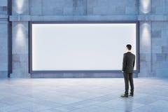 Man looking at blank billboard. Businessman looking at blank billboard outside at night. Mock up, 3D Rendering Royalty Free Stock Photo
