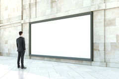 Man looking at blank billboard. Thoughtful businessman looking at blank billboard outside in daylight. Mock up, 3D Rendering Royalty Free Stock Images