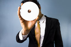 Man looking through blank DVD. Man in black suit looking through blank DVD Royalty Free Stock Photos