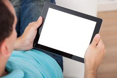 Man looking at blank screen of digital tablet. Closeup of mid adult man looking at blank screen of digital tablet at home Royalty Free Stock Photo