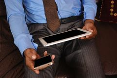 Man looking at blank tablet pc screen and blank mobile screen Stock Image
