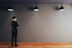 Man looking at blank wall. Thoughtful businessman looking at empty black concrete wall in room with wooden floor and ceiling with lamps. Mock up, 3D Rendering Royalty Free Stock Photo
