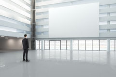 Man looking at a blank white banner in a large bright hall, mock Royalty Free Stock Image