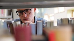 Man Looking For Book On Bookshelves At Library At College