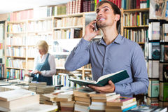 Man looking at book and talking on mobile phone. Young cheerful men looking at book and talking on mobile phone in book store Royalty Free Stock Photo
