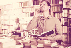 Man looking at book and talking on mobile phone. Young cheerful men looking at book and talking on mobile phone in book store Royalty Free Stock Image