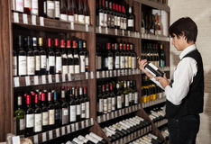 Man looking at bottle of wine in shop. wine shopping Stock Photography