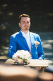 Man Looking at Bouquet at Table. Man sitting at table and looking at bouquet Royalty Free Stock Photography