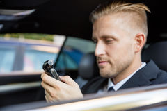 Man Looking At Breathalyzer Test. Man Sitting Inside Car Looking At Breathalyzer Test Royalty Free Stock Photography