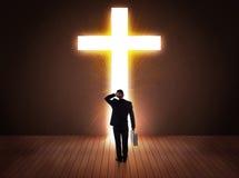 Man looking at bright cross sign Stock Image