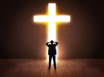 Man looking at bright cross sign Stock Photography