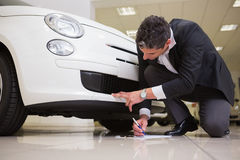 Man looking at the bumper while writing on clipboard Stock Image