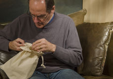 Man looking into burlap bag Royalty Free Stock Photos