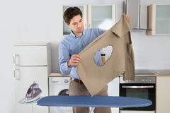 Man Looking At Burned Cloth With Electric Iron Royalty Free Stock Images