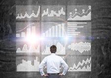Man looking at business charts. Businessman looking at business charts on grid. Concrete wall background Royalty Free Stock Photos
