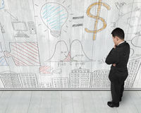 Man looking at business concept doodles on wooden wall Royalty Free Stock Images