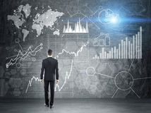 Man looking at business diagrams. Businessman looking at global business charts and map on chalkboard background royalty free stock photography
