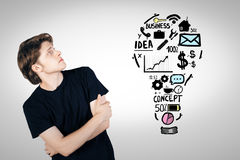 Man looking at business sketch. Handsome young man looking at light bulb shaped business sketch on light background. Idea concept Royalty Free Stock Photo