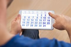 Man looking at calendar on cellphone Stock Image
