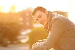Man looking at camera in a balcony in winter. Serious man looking at camera in a balcony in winter at sunset royalty free stock photos