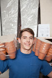 Man looking at the camera with flower pots. Seller man showing some flower pots stock photography