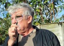 Man looking at camera through a magnifier lens.. Stock Photo