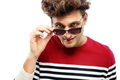 Man looking at the camera through sunglasses. Portrait of a trendy man looking at the camera through sunglasses Stock Photos
