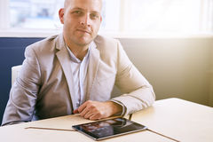 Man looking at camera with tablet in front of him stock image