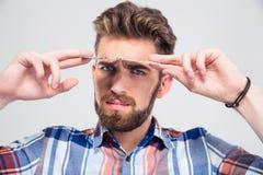 Man looking at camera from under dollar bill Stock Images