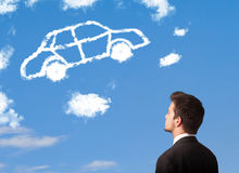 Man looking at car cloud on a blue sky. Handsome young man looking at car cloud on a blue sky royalty free stock images