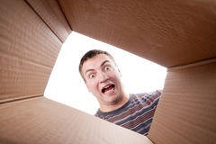 Man looking into cardboard box. Surprised young man looking into cardboard box Stock Photography