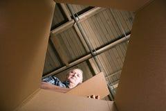 Man looking in cardboard box Stock Photo
