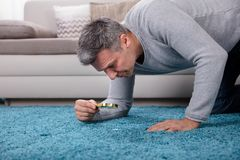 Man Looking At Carpet Through Magnifying Glass. Side View Of A Mature Man Looking At Blue Carpet Through Magnifying Glass royalty free stock photos