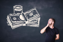 Man looking at cash sketch. Thoughtful casual young man looking at cash sketh on blackboard background Royalty Free Stock Image